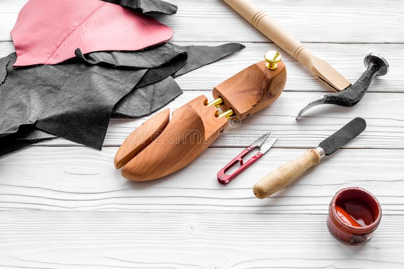 Clobber`s desk. Tools, wooden last, pieces of leather on white wooden background copyspace. Clobber`s desk. Tools, wooden last, pieces of leather on white wooden stock photo