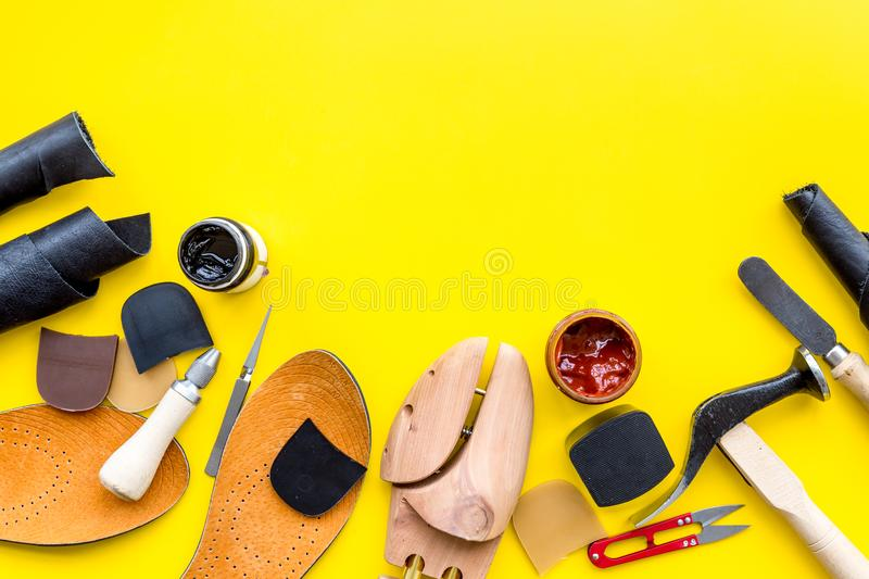 Clobber tools. Hummer, awl, knife, sciccors, wooden shoe, paint and leather. Yellow background top view space for text. Clobber tools on yellow background top stock image