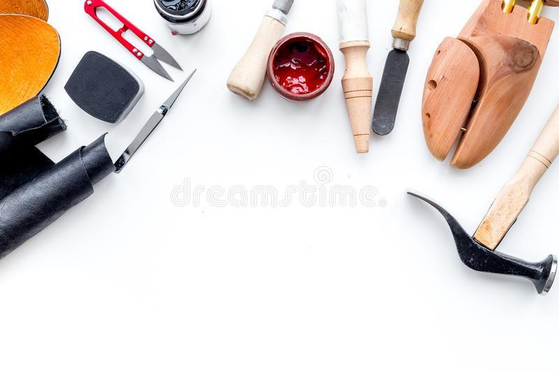 Clobber tools. Hummer, awl, knife, sciccors, wooden shoe, paint and leather. White background top view space for text. Clobber tools on white background top view stock photo