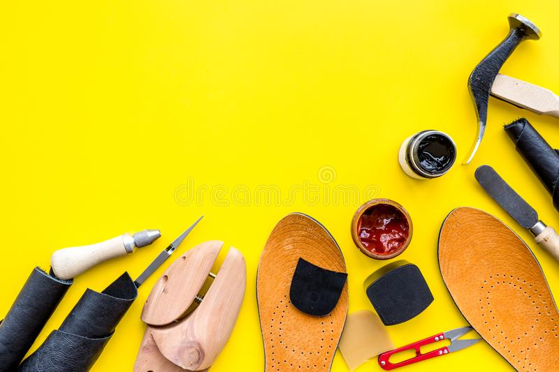 Clobber tools. Hummer, awl, knife, sciccors, wooden shoe, paint and leather. Yellow background top view space for text. Clobber tools on yellow background top stock photo