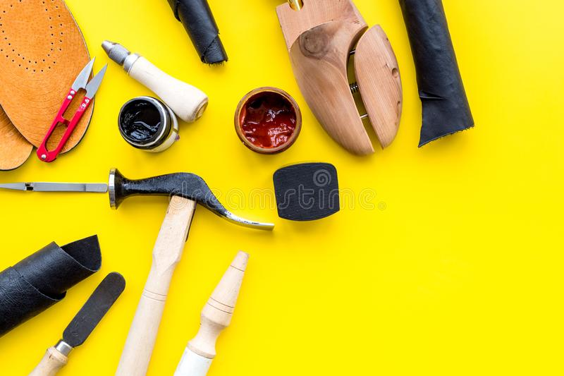 Clobber tools. Hummer, awl, knife, sciccors, wooden shoe, paint and leather. Yellow background top view space for text. Clobber tools on yellow background top royalty free stock photos