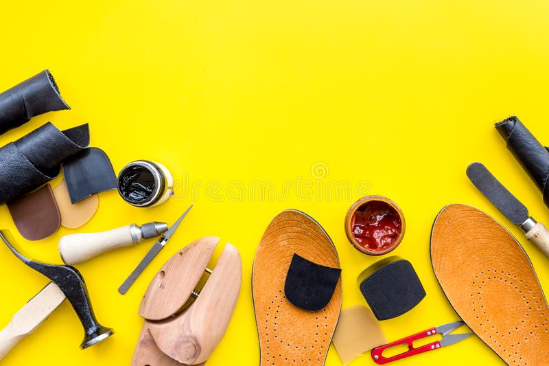 Clobber tools. Hummer, awl, knife, sciccors, wooden shoe, paint and leather. Yellow background top view space for text. Clobber tools on yellow background top stock photos