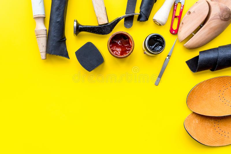 Clobber tools. Hummer, awl, knife, sciccors, wooden shoe, paint and leather. Yellow background top view space for text. Clobber tools on yellow background top royalty free stock images