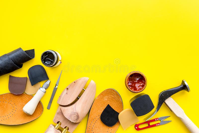 Clobber tools. Hummer, awl, knife, sciccors, wooden shoe, paint and leather. Yellow background top view space for text. Clobber tools on yellow background top stock images