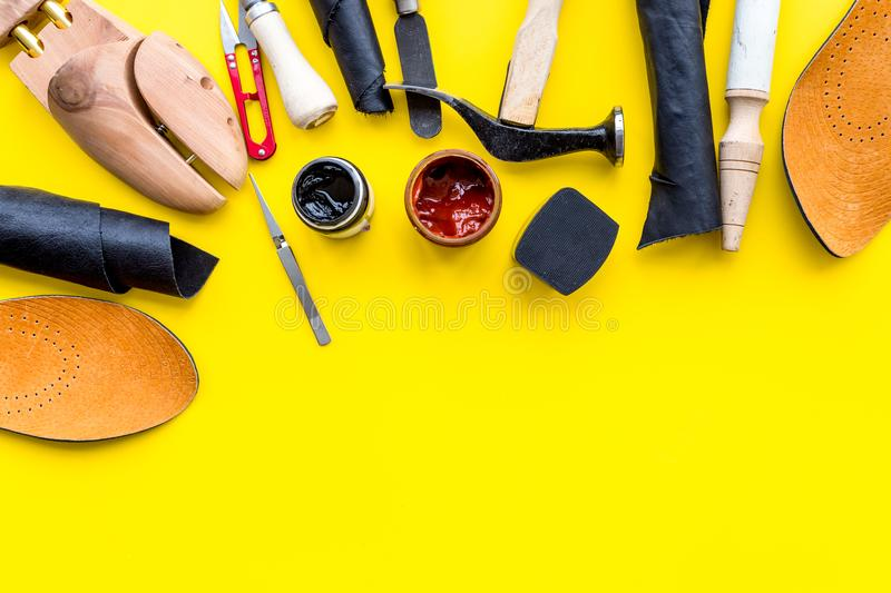 Clobber tools. Hummer, awl, knife, sciccors, wooden shoe, paint and leather. Yellow background top view space for text. Clobber tools on yellow background top royalty free stock image