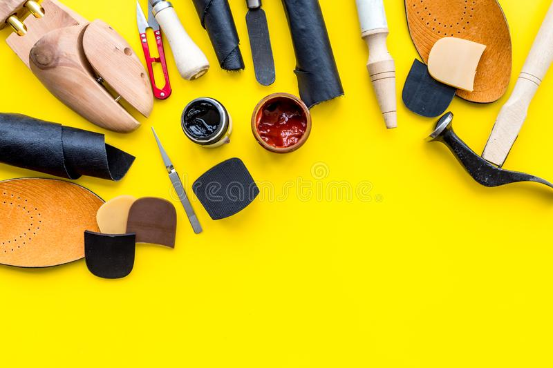 Clobber tools. Hummer, awl, knife, sciccors, wooden shoe, paint and leather. Yellow background top view space for text. Clobber tools on yellow background top stock photography