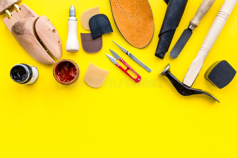 Clobber tools. Hummer, awl, knife, sciccors, wooden shoe, paint and leather. Yellow background top view space for text. Clobber tools on yellow background top royalty free stock photo