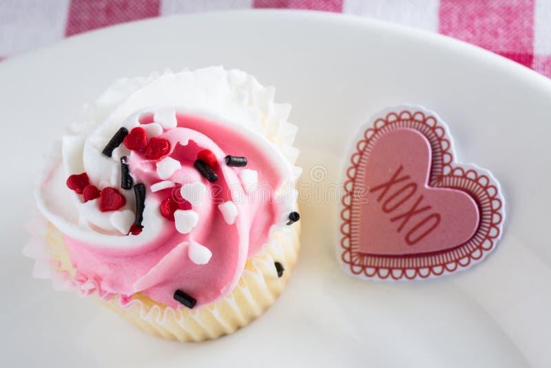 Cloce encima de la magdalena y de la muestra del día de tarjetas del día de San Valentín imagen de archivo