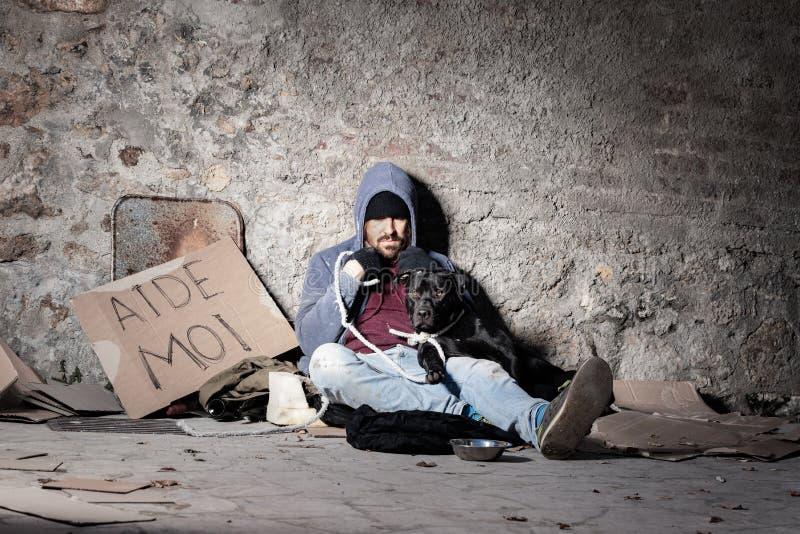 Clochard-Mann mit seinem Hund, der auf der Straße sitzt lizenzfreie stockfotos