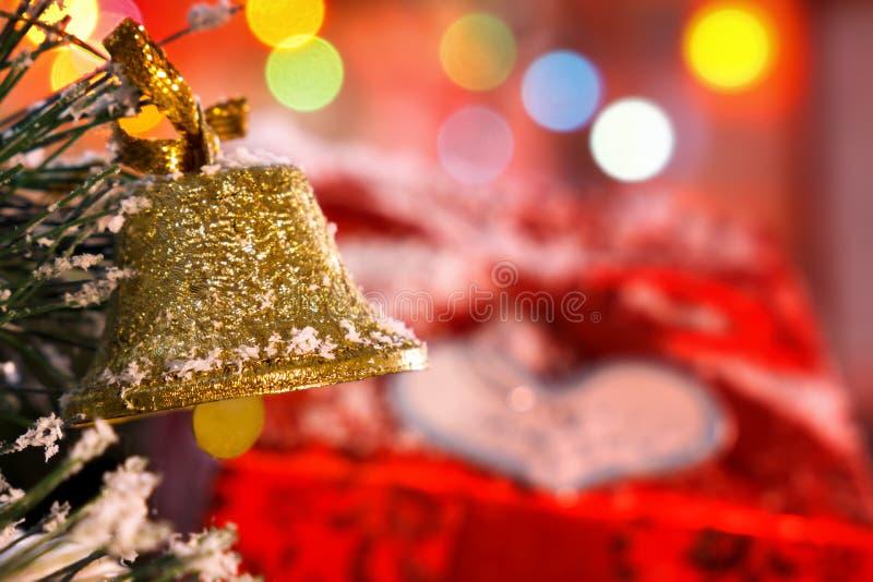 Cloche de Noël accrochant sur une branche sur un fond de cadeau Bokeh Un bon nombre d'espace pour le texte image libre de droits