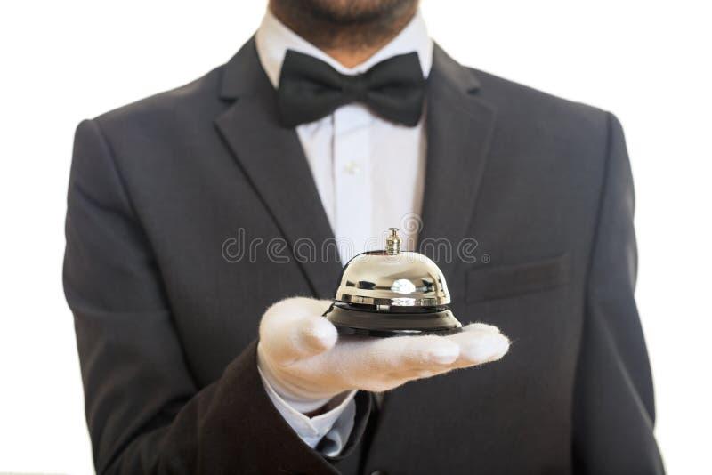 Cloche de service de Butler dans une main enfilée de gants images stock