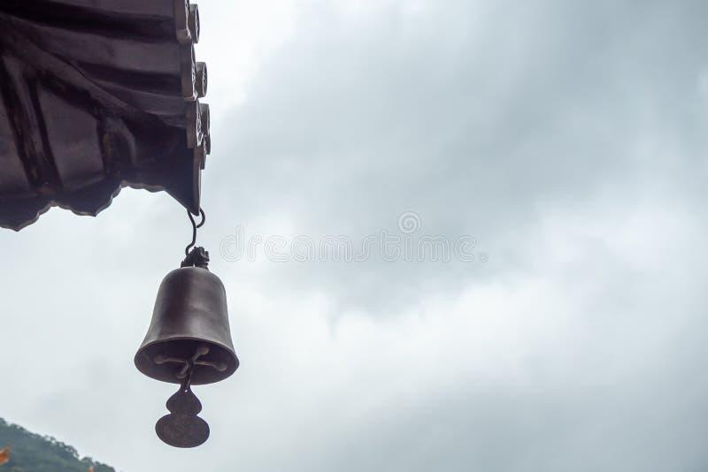 Cloche en laiton pendant du toit de temple sur le fond obscurci de ciel photo libre de droits