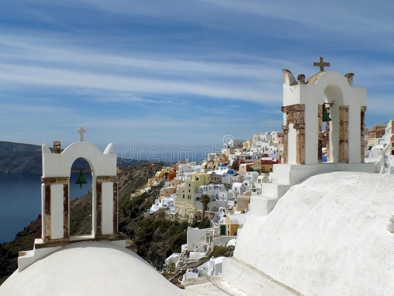 Cloche-tours traditionnelles d'église d'îles grecques et le paysage impressionnant du village d'Oia, île de Santorini image libre de droits