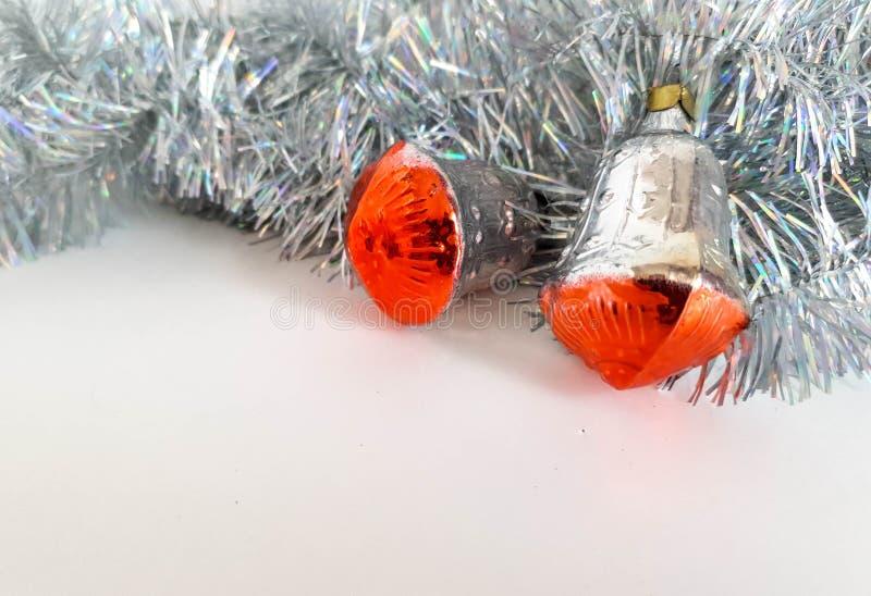 Cloches argentées avec le fond rouge en tant que jouets de décoration de Noël sur le fond blanc image libre de droits