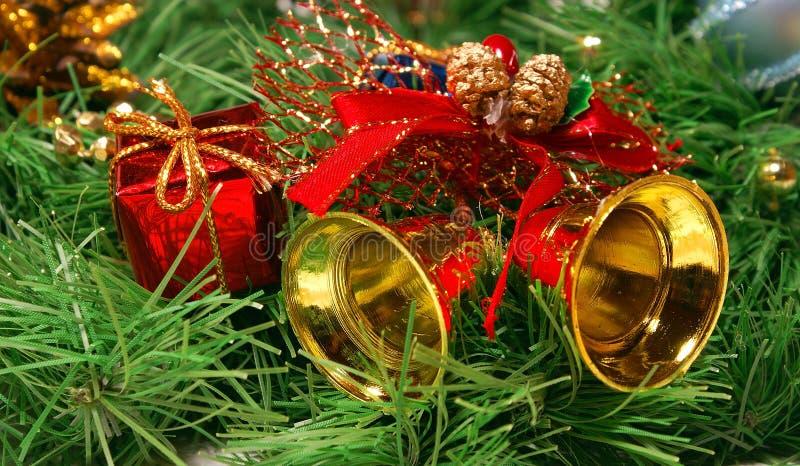 Cloches d'or contre le branchement d'arbre de Noël photographie stock libre de droits