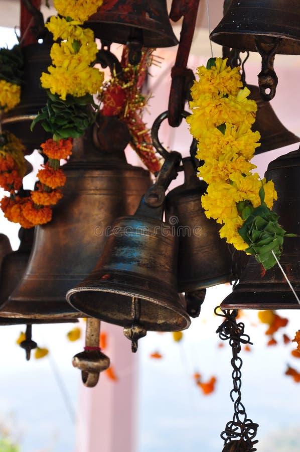 Cloches et fleurs de dévotion dans un temple hindou photographie stock libre de droits