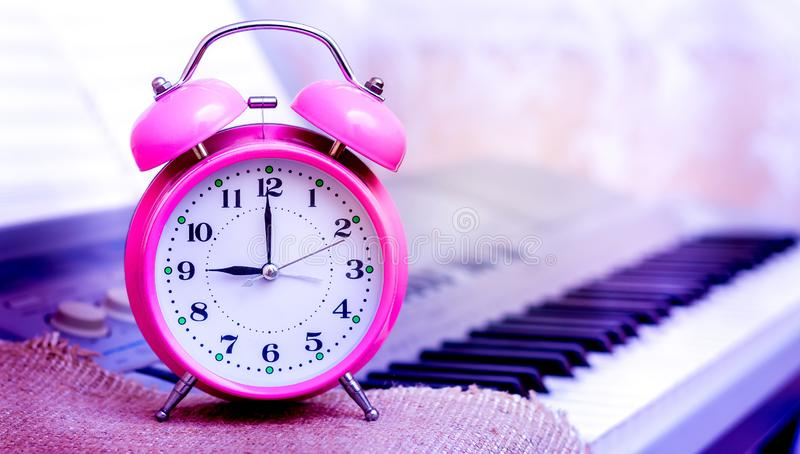 Clock against piano background. Reminder about the beginning of the music lesson. It`s time to start the game royalty free stock photo