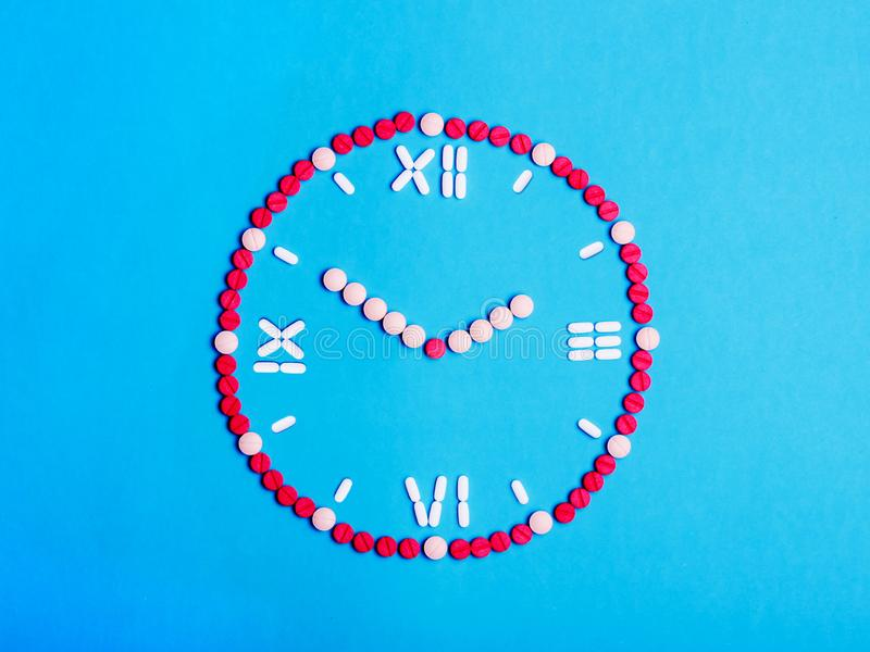 Clock with arrows from medical tablets and pills. Health concept stock photos