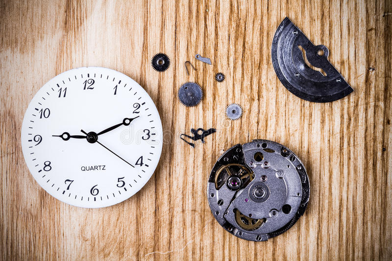 Clock background. Various clock parts (cogs, hands, springs) laid on a rustic/antique wood background, viewed from above stock image