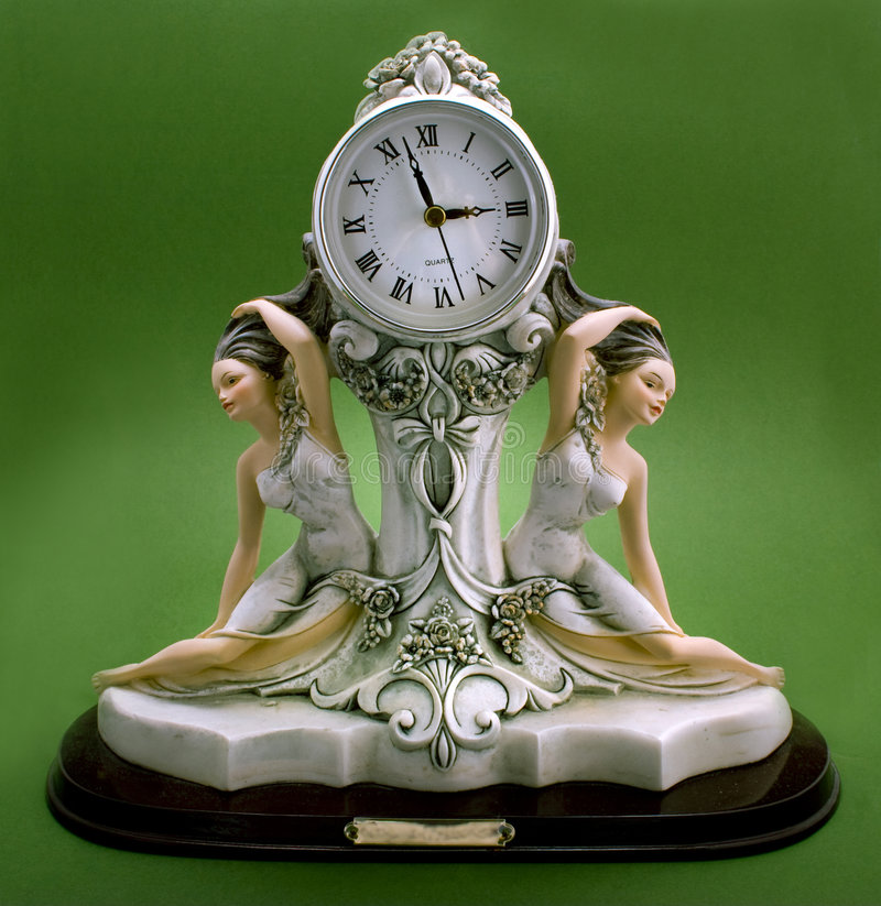 Clock with beautiful girls statuette. Close-up isolated on a green background royalty free stock photography