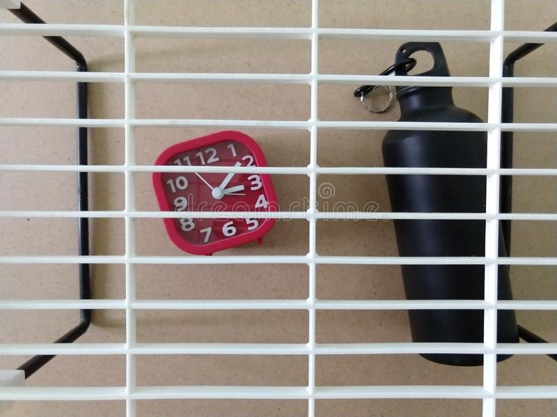 A clock and black bottle. Clock and black bottle with hook and plstic abstrac interior royalty free stock image