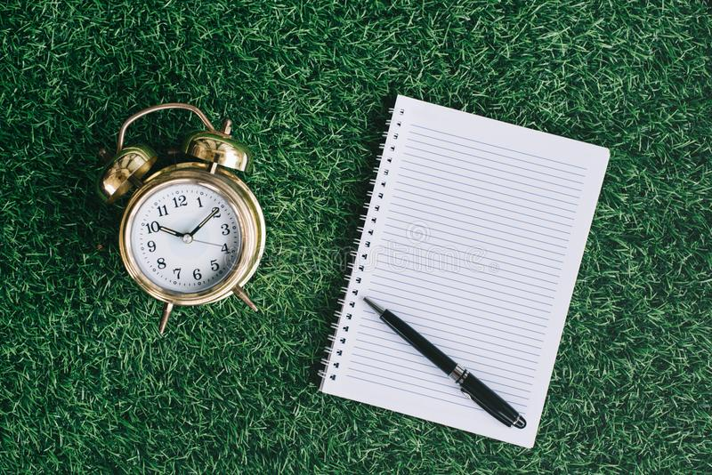 Clock and blank notebook on a green grass stock image