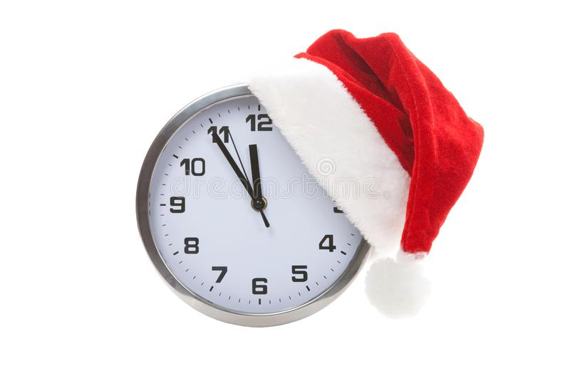 Clock with christmas santa hat isolated on white background. Happy xmas hollidays. Santa hat and clock at studio. Christmas stock images