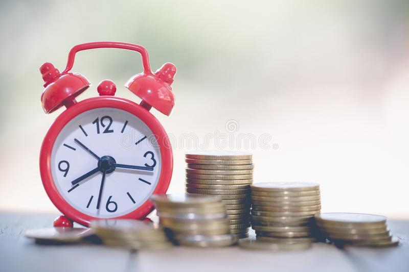 Clock with coin  on table. Time investment or retirement saving. Save money for future use. Business and finance concepts stock photo