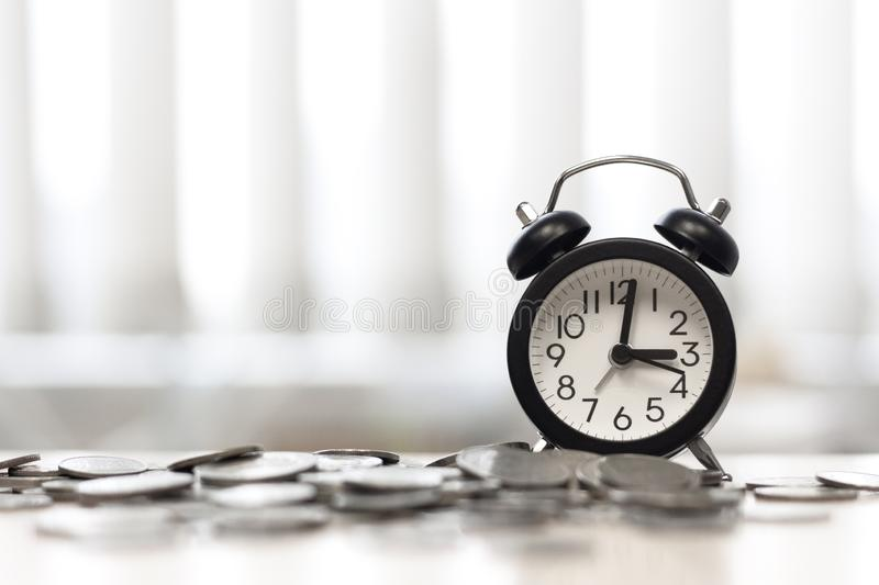 Clock and coins on desk table area window, Time is money stock image
