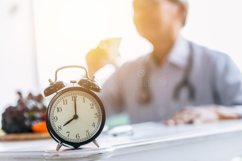 Clock on doctor clinic table for times to healthcare royalty free stock photos