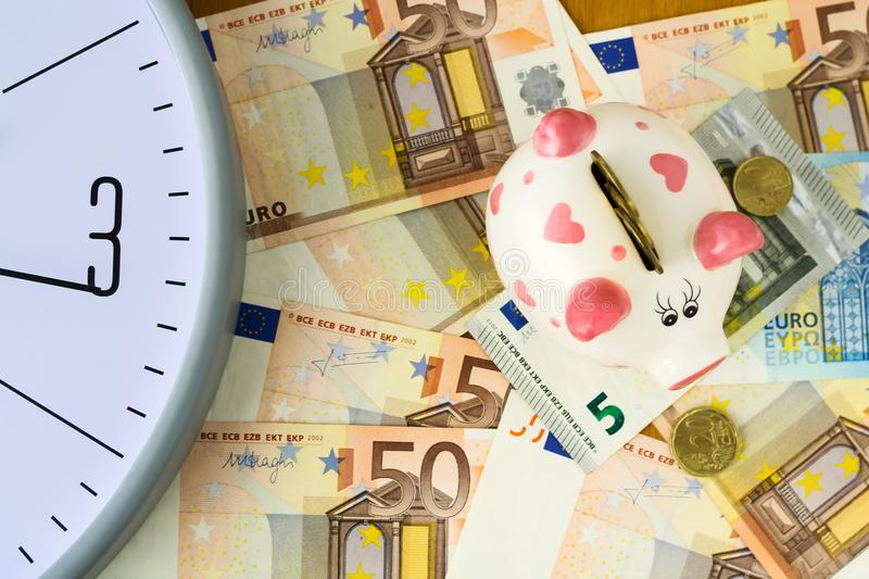 Clock, Euro banknotes and piggy bank. Concept time is money. View from above. Business, finance. stock images