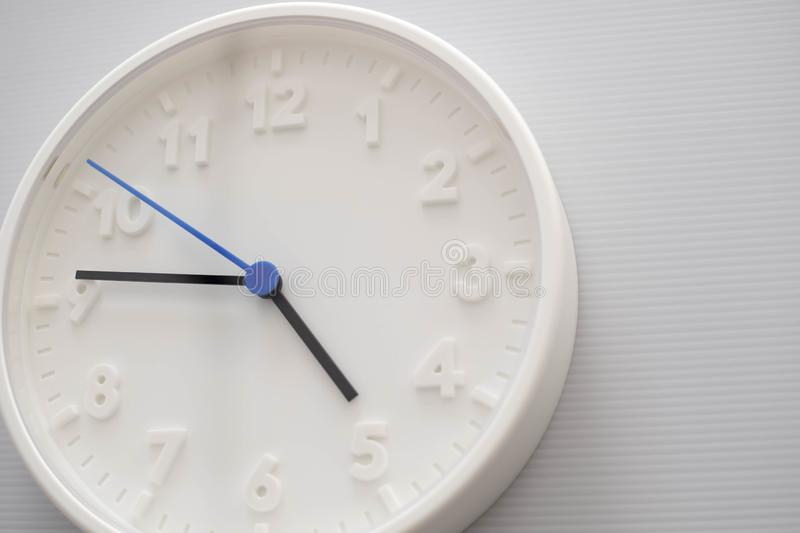Clock face showing five o`clock with white background. White round wall clock. Five o`clock. off for work. 5 a.m. or 5 p.m. Clock face showing five o`clock with stock photo