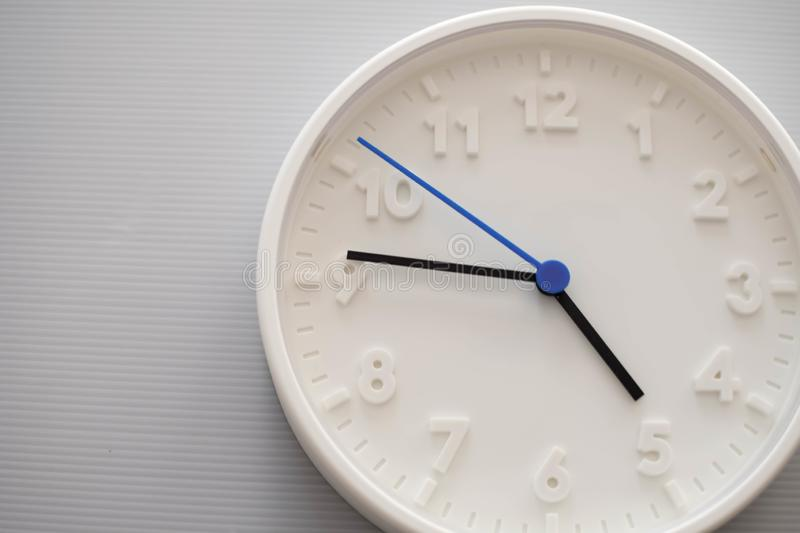 Clock face showing five o`clock with white background. White round wall clock. Five o`clock. off for work. 5 a.m. or 5 p.m. Clock face showing five o`clock with stock photography