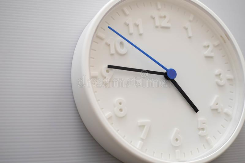 Clock face showing five o`clock with white background. White round wall clock. Five o`clock. off for work. 5 a.m. or 5 p.m. Clock face showing five o`clock with stock photos