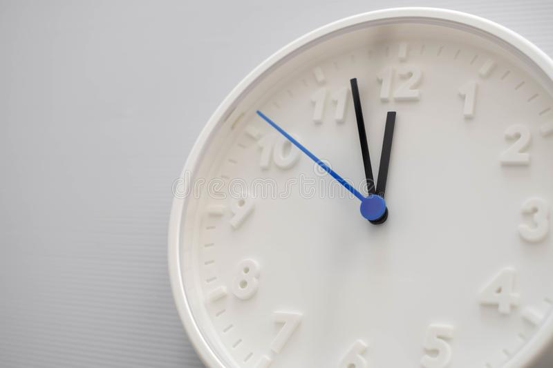 Clock face showing twelve o`clock with white background. White round wall clock. Twelve o`clock. Midday or midnight. 12 a.m. or. 12 pm royalty free stock image