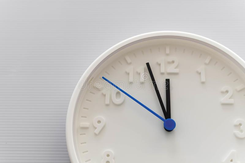 Clock face showing twelve o`clock with white background. White round wall clock. Twelve o`clock. Midday or midnight. 12 a.m. or. 12 pm royalty free stock images