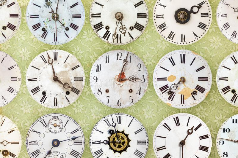 Clock faces in front of retro wallpaper. Collection of vintage clock faces in front of retro wallpaper stock photo
