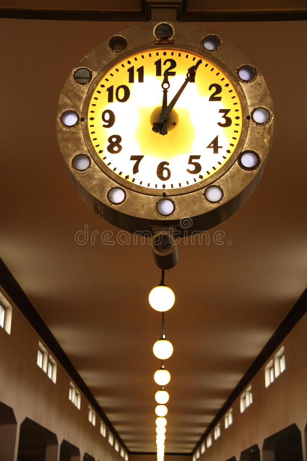 Clock in factory hall. Luminous yellow clock in old factory hall stock image