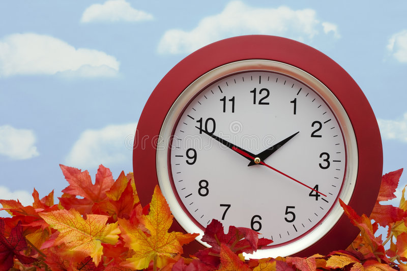 Clock on Fall Leaves. Red clock on fall leaves � the fall time change royalty free stock photo