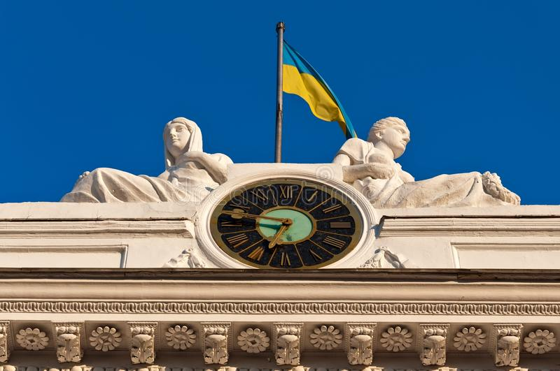 Clock and Flag. Fragment of a facade of a building of the Odessa city council - chiming clock, sculptural composition and a national flag of Ukraine stock photography