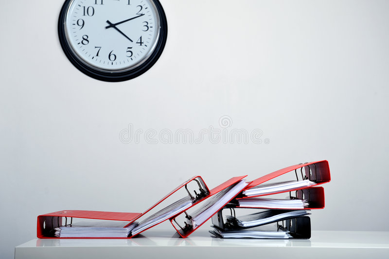 Clock, folders and deadline. Stack of red folders on desk and a clock in background, deadline concept stock images