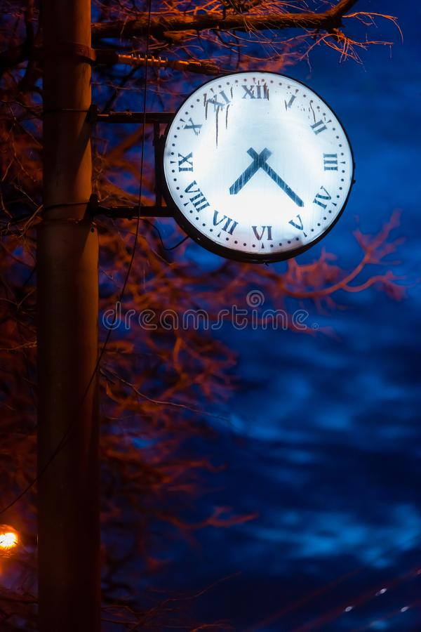 A clock with a glowing dial on a street lamppost at dusk royalty free stock photo