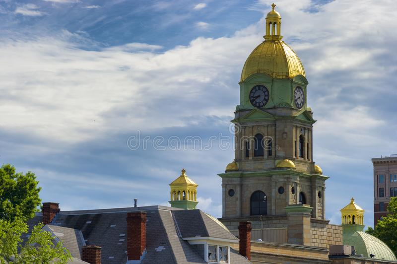 Cabell County Court House golden dome. Clock and golden dome of Huntington West Virginia`s, Cabell County Court House rises above the roof tops of other royalty free stock images