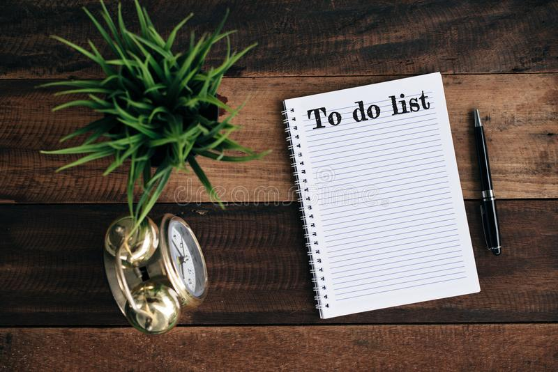 Clock, green plant, pen and notebook with TO DO LIST word stock images