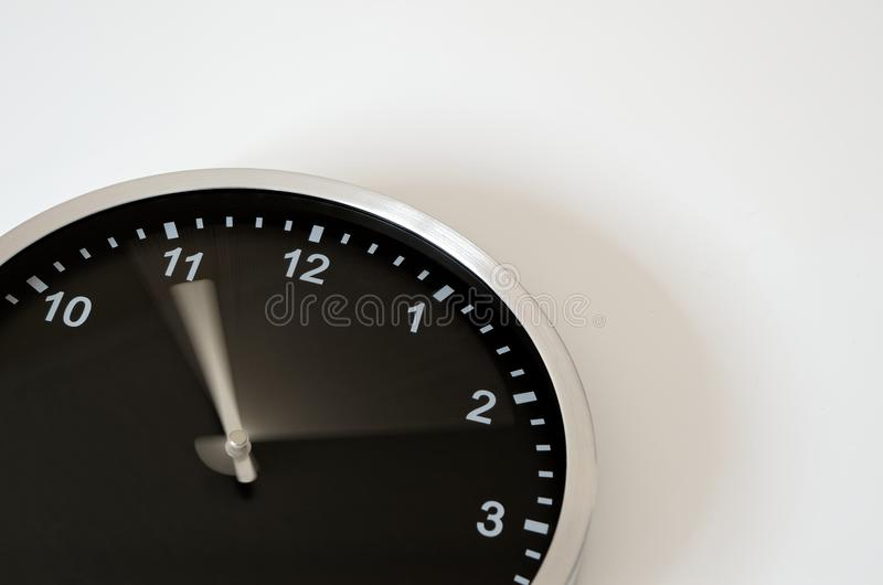 Moving clock hand of the black wall clock. Clock hand is moving from five to eleven till ten past eleven. Black wall clock on white background royalty free stock photo