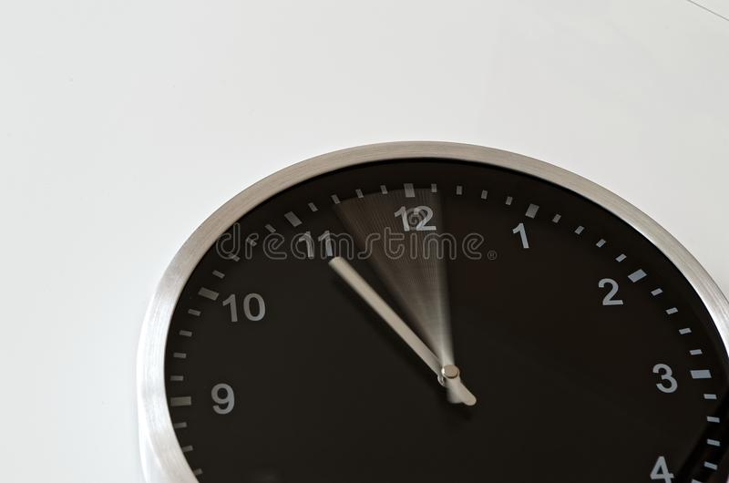 Clock hand moving to eleven o clock. Clock hand is moving from five to eleven till eleven o clock. Black wall clock on white background royalty free stock photos