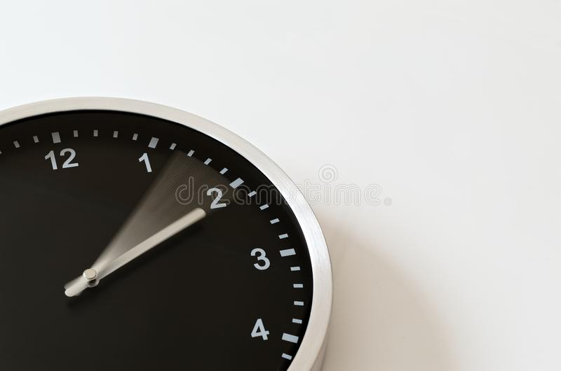 Clock hand moving to quarter past two. Clock hand is moving to quarter past two. Black wall clock on white background stock photos