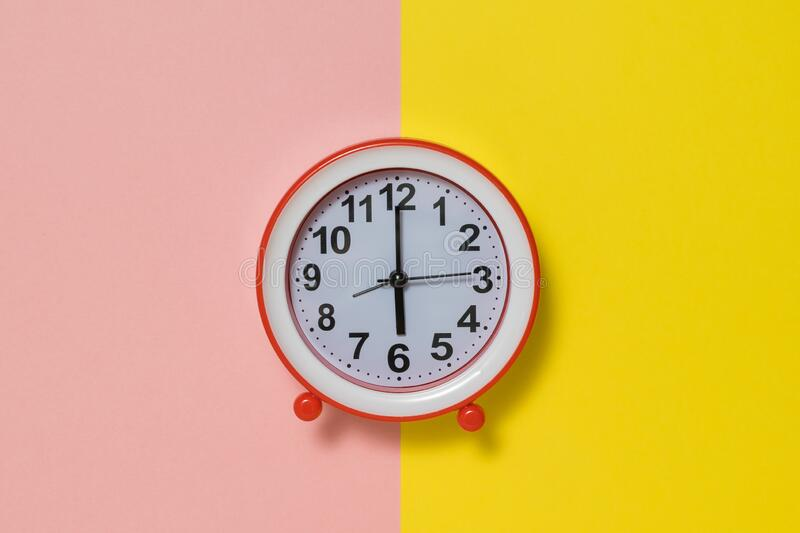 Clock with hands on a yellow and pink background. stock image