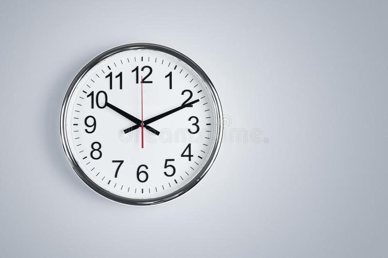 Clock hanging at the wall stock image