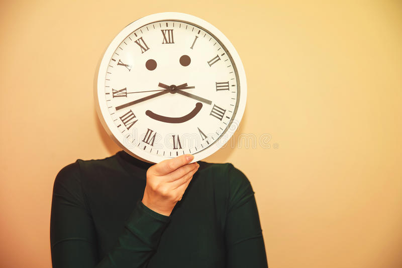 Clock instead of a head. A woman with a clock instead of a head stock photography